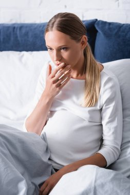 Selective focus of pregnant woman touching mouth on bed stock vector