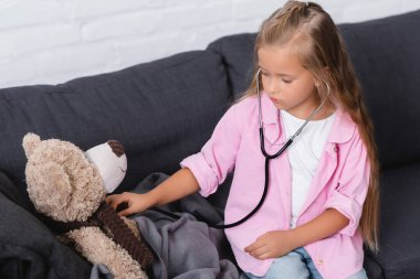 Child holding stethoscope near soft toy while sitting on sofa stock vector
