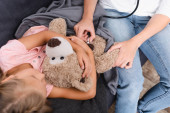 Overhead view of girl hugging soft toy near mother with stethoscope