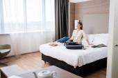 selektivní zaměření mladé ženy při pohledu pryč v blízkosti notebooku a zavazadel na posteli v hotelu