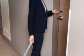 cropped view of businesswoman in suit holding room card while unlocking door in hotel