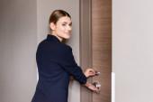 freudige Geschäftsfrau im Anzug hält Zimmerkarte in der Hand, während sie Tür im Hotel aufschließt