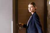 businesswoman in suit holding room card while unlocking door in hotel
