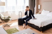 selective focus of businesswoman in suit talking on smartphone while sitting on bed near luggage in hotel