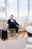 junge Geschäftsfrau im Anzug spricht auf Smartphone, während sie im Sessel neben dem Gepäck im Hotel sitzt