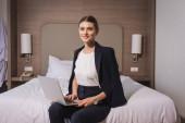 freudige Frau im Anzug sitzt auf Bett mit Laptop im Hotelzimmer