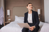 joyful woman in suit sitting on bed with laptop and looking away in hotel room