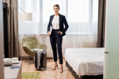 selective focus of young businesswoman standing with hand in pocket and holding laptop near travel bag in hotel room