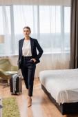 mladá podnikatelka stojící s rukou v kapse a držící notebook v blízkosti cestovní tašky v hotelovém pokoji
