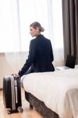 mladá podnikatelka v obleku sedí na posteli v blízkosti notebooku s prázdnou obrazovkou a kufrem v hotelovém pokoji