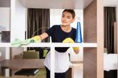 pokojská v zástěře a gumové rukavice hadr při čištění police v hotelovém pokoji