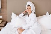 potěšená žena v ručníku a bílém županu ležící na posteli v hotelovém pokoji