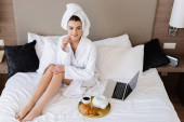 vysoký úhel pohledu na mladou ženu v županu sedí v blízkosti notebooku a podnos se snídaní na posteli