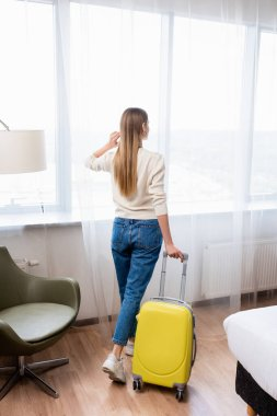 Back view of young woman standing with yellow luggage in hotel room stock vector