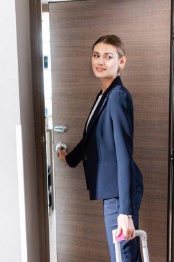 Joyful businesswoman in suit opening door in hotel stock vector