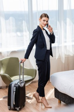 Businesswoman in suit standing with baggage while talking on smartphone in hotel room stock vector