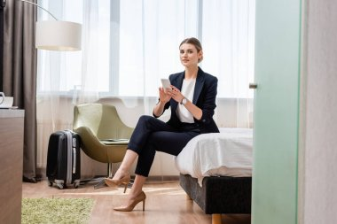 Young businesswoman in suit holding smartphone while sitting on bed neat travel bag in hotel room stock vector