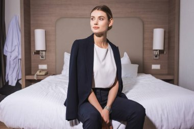 Young businesswoman in suit looking away and sitting in bed on hotel stock vector