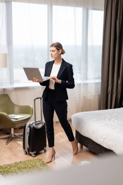 Young businesswoman standing and using laptop near travel bag in hotel room stock vector