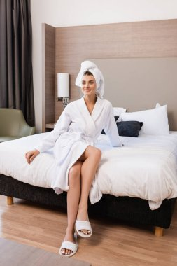 Joyful woman in towel and white bathrobe sitting on bed in hotel room stock vector