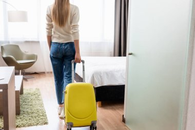 Back view of woman in jeans standing with yellow luggage in hotel room stock vector