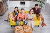 KYIV, UKRAJINA - 28. června 2020: pohled z velké perspektivy na multikulturní přátele držící pivo a hrající videohry u pizzy na stole