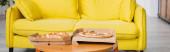 panoramatická plodina lahodné pizzy na stole v blízkosti žluté pohovky