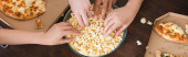 partial view of multicultural friends taking popcorn from bowl during party, horizontal concept
