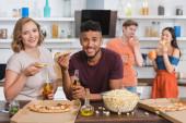 potěšeni multietnické přátelé při pohledu na kameru při jídle pizzy během párty