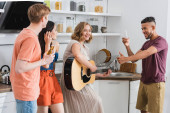 selektivní zaměření vzrušený africký americký muž ukazující palec nahoru, zatímco mladá žena hraje na kytaru pro multikulturní přátele