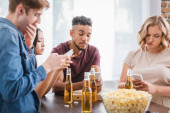 selective focus of multiethnic friends chatting on mobile phones near beer and popcorn during party