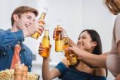 szelektív fókusz többnemzetiségű barátok koccintás üveg sör a party