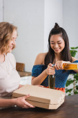 mladá žena držení pizza box poblíž asijské přítel otevření piva během párty
