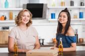mladé multikulturní ženy při pohledu na kameru v blízkosti piva a pizza box na stole