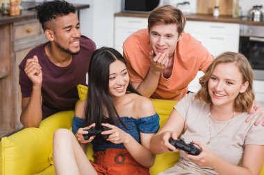 KYIV, UKRAINE - JULY 28, 2020: excited multicultural friends playing video game during party stock vector