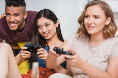 KYIV, UKRAINE - JULY 28, 2020: selective focus of multiethnic friends playing video game during party stock vector