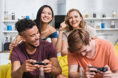 KYIV, UKRAINE - JULY 28, 2020: selective focus of excited asian woman showing winner gesture near multicultural friends playing video game stock vector