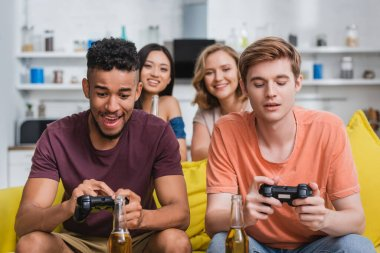 KYIV, UKRAINE - JULY 28, 2020: multicultural friends playing video game during party in kitchen stock vector