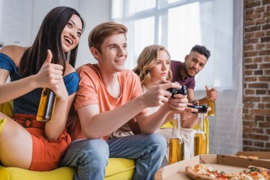 KYIV, UKRAINE - JULY 28, 2020: excited asian woman holding beer and showing thumb up near friends playing video game stock vector