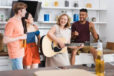 Selective focus of young woman playing guitar for excited multicultural friends stock vector