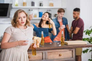Selective focus of young woman with beer and smartphone looking at camera near multicultural friends on background stock vector