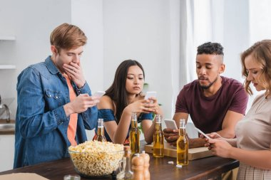 Selective focus of multiethnic friends using mobile phones near beer and popcorn during party stock vector