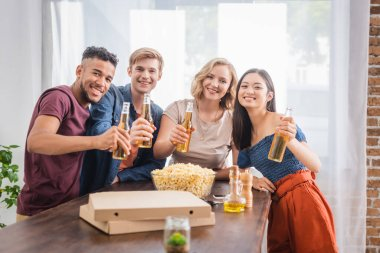 Joyful multiethnic friends looking at camera while holding bottles of beer stock vector