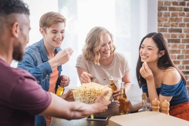 Excited multiethnic friends eating popcorn and talking during party stock vector