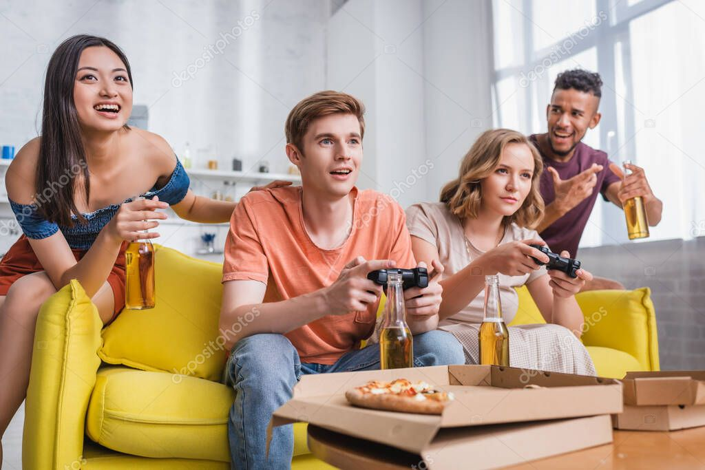 KYIV, UKRAINE - JULY 28, 2020: excited asian woman and african american man holding bottles of beer near friends playing video game stock vector