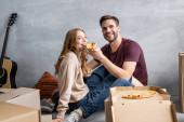 Jubelnder Mann füttert Freundin mit Pizza in Pappkartons, bewegendes Konzept