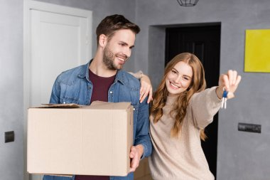 Joyful woman holding keys near boyfriend with box stock vector