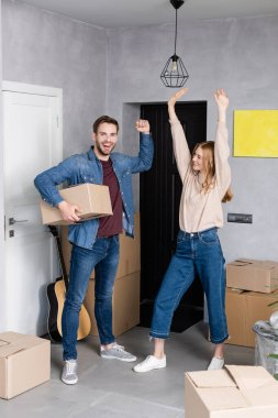 Excited man holding carton box near pleased woman standing with hands above head, relocation concept stock vector