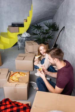 Woman with open mouth looking at boyfriend with pizza in hands near carton boxes stock vector