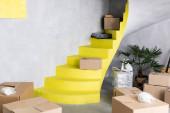 Kartons auf gelben Treppen in neuer Wohnung, Umzugskonzept